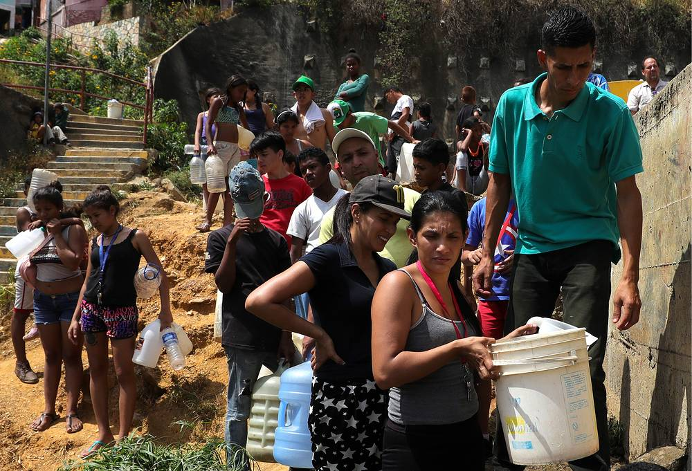 People wait in line to get drinking water as water supply is disrupted in some neighbourhoods due to power outage in Caracas