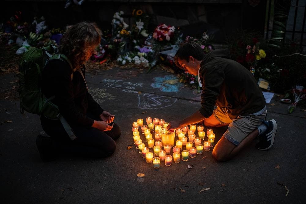 People lighting candles next to flowers and tributes laid by the wall of the Botanic Gardens in Christchurch, New Zealand, March 17. 50 people are confirmed dead, with 36 injured still in hospital following shooting attacks on two mosques in Christchurch on March 15. The attack is the worst mass shooting in New Zealand's history