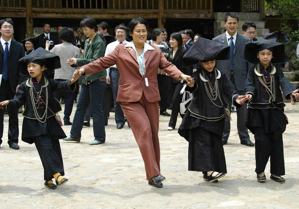 Thai Princess Maha Chakri Sirindhorn dancing with children of Zhuang ethnic group at Tunli Village of Napo County, China's Guangxi Zhuang Autonomous Region, 2006
