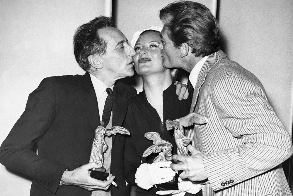 Jean Cocteau and Jean Marais kissing Michele Morgan whilst holding their awards at Cannes Film Festival, 1951