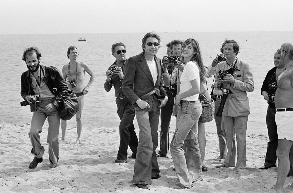 French song writer and composer Serge Gainsbourg and his wife Jane Birkin are surrounded by photographers, Cannes, 1974
