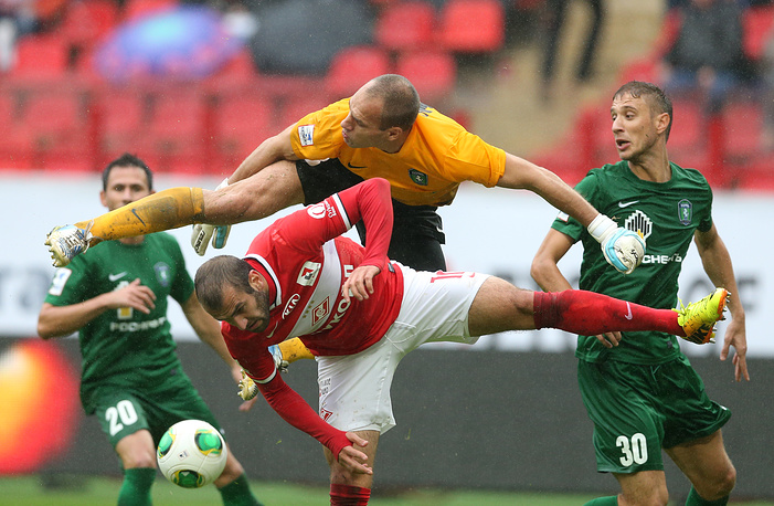 FC Spartak Moscow forward Yura Movsisyan (bottom) and Tom' goalie Petr Vashek (top), during Russian Soccer Championship game. September 1, 2013.