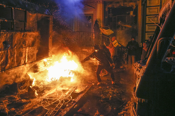 A protester warms himself near a fire as they clash with riot police during an anti-government protest in downtown Kiev