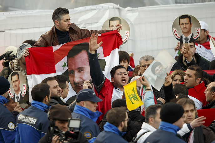Pro Syrian President Bashar al-Assad supprters protest near the hotel, during the opening of the Geneva II peace talks, in Montreux, Switzerland, 22 January 2014