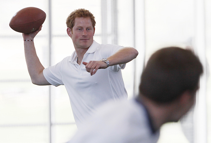 Prince Harry throwing a football during a meeting with injured American and British servicemen on a US visit in May 2013