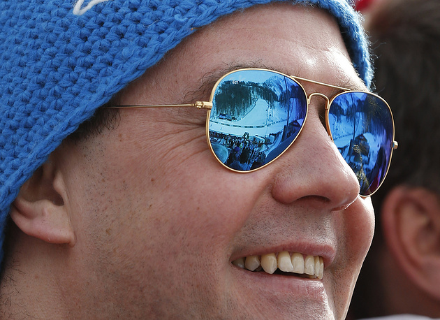 Russian Prime Minister Dmitry Medvedev watches the men's Downhill race as the reflection in his sunglasses indicates