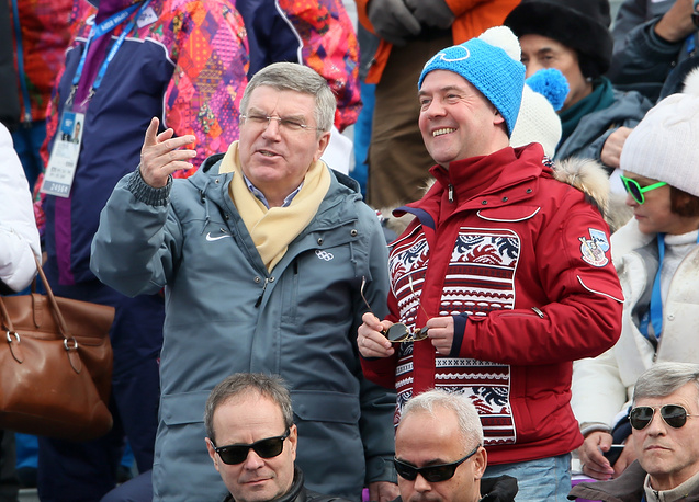 Russian Prime Minister Dmitry Medvedev (R) and President of the International Olympic Committee (IOC) Thomas Bach watch the Men's Downhill