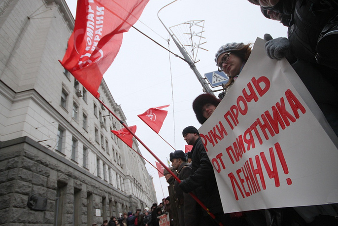 """Protesters hold a sign saying """"Hands off the Lenin monument"""""""