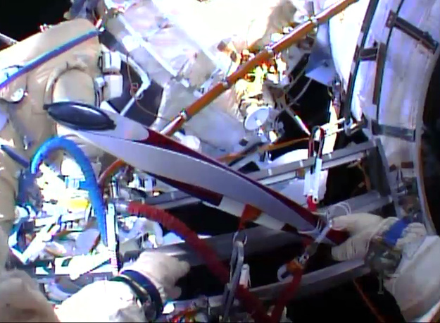 Sochi Olympic torch being held during a spacewalk