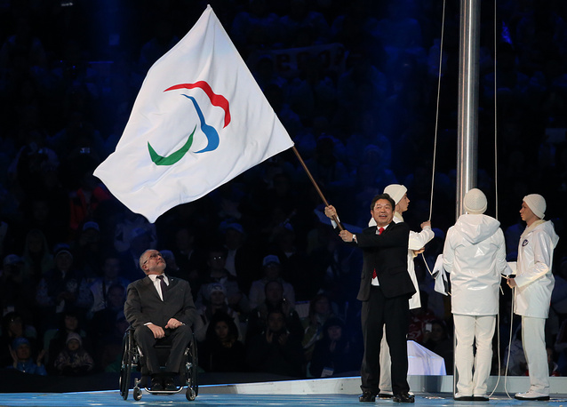 President of the International Paralympic Committee Philip Craven passes the Paralympic flag on to Mayor of Pyeongchang