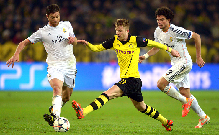 Dortmund's Marco Reus (C) and Madrid's Xabi Alonso vie for the ball