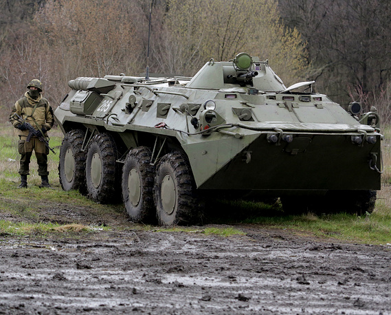A Ukrainian soldier participating in the enti-riot operation behind a military vehicle