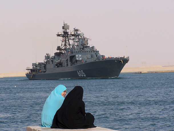 Photo: Two women sit along the Suez Canal as the Russian missile destroyer Admiral Chabanenko crosses the canal 100 km east of Cairo, Egypt