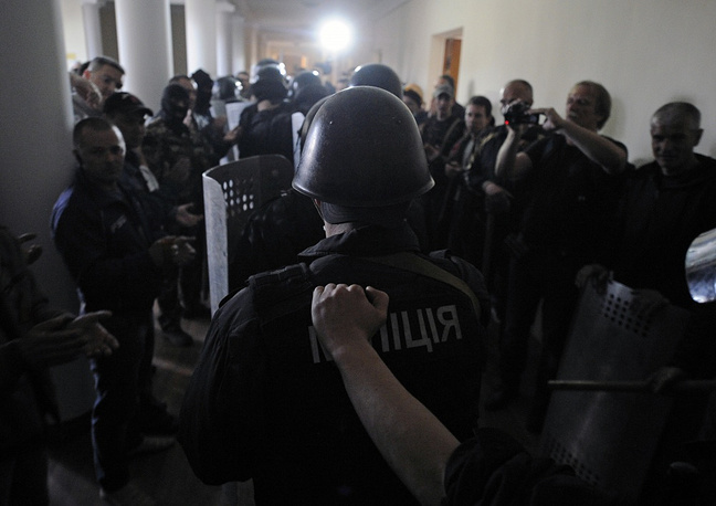 Law enforcement officers leave the regional administration building, while the protester applaud