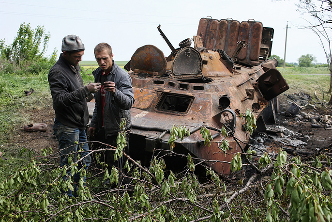 Local residents near a burnt out military vehicle in the aftermath of a military clash between Donetsk Region militia and the Ukrainian government's forces not far from Kramatorsk