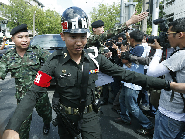 Thai armed soldiers guard the van of Niwatthamrong Boonsongpaisan as he arrives at the Army Club in Bangkok