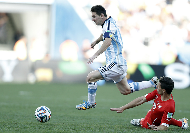 Lionel Messi (L) of Argentina in aciton against Fabian Schaer of Switzerland