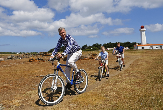 Belgian King Philippe cycles with his children Gabriel (right) and Emmanuel during a family holiday on the Island of Yeu, southwestern France