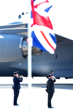 A Dutch military musician plays the Last Post at the airbase in Eindhoven after the arrival of a Dutch Air Force C-130 Hercules plane and an Australian Royal Australian Air Force C17 transport plane