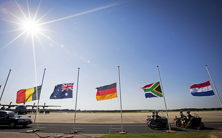 Flags of Belgium, Australia, Germany, South Africa and The Netherlands as the column of funeral hearses leaves the airbase in Eindhoven