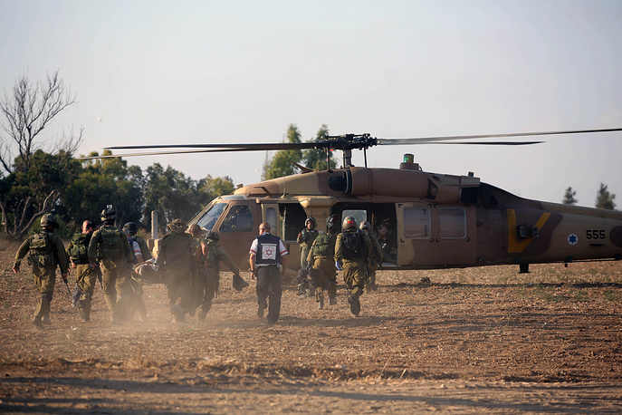 Israeli soldiers evacuate a wounded soldier in a helicopter after a mortar shell attack