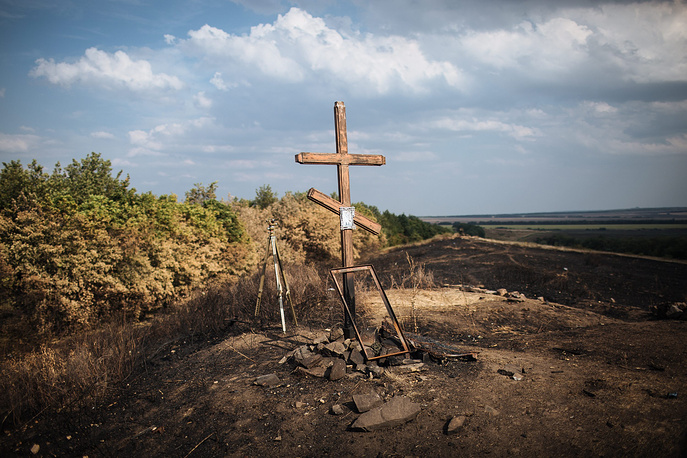 A cross is placed on a burnt out field in Ukraine's Donetsk Region