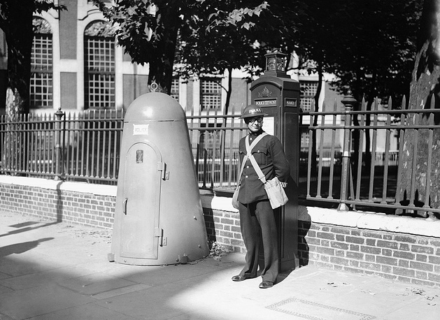 A London policeman stands next to a one-person bomb shelter, September 6, 1939
