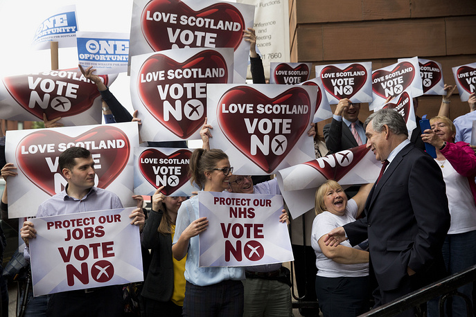 No campaign supporters holding up posters to greet former British Prime Minister and No campaigner Gordon Brown