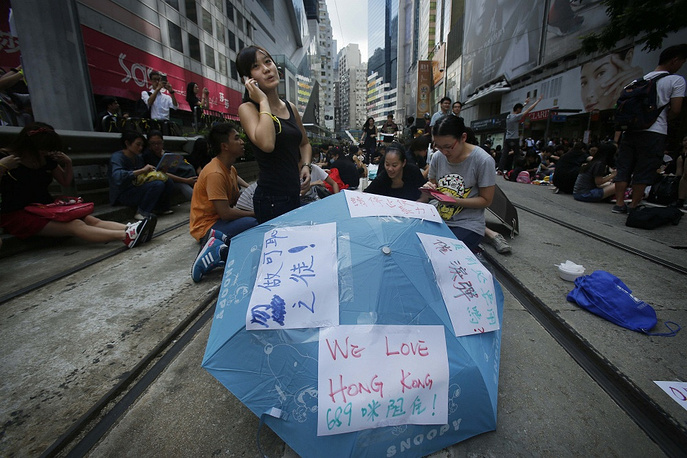 """The movement has been already labeled """"the Umbrella Revolution"""" for the umbrellas that many people are holding to protect themselves from pepper spray and tear gas, as well as to cope with oppressive heat"""
