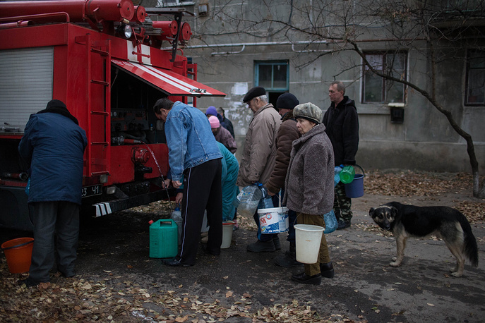 According to the United Nations, more than 4,000 people have been killed and hundreds of thousands have fled Ukraine's southeast as a result of clashes between Ukrainian troops and local militias in the Donetsk and Luhansk regions. Photo: Local residents fill their buckets with water from a firefighting vehicle in Slavyanoserbsk, Luhansk region