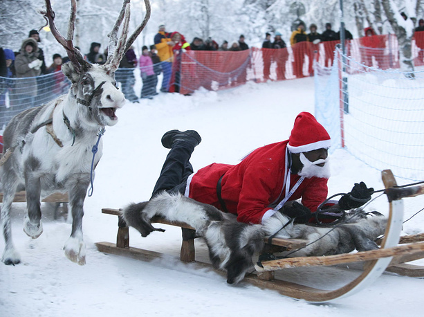 Photo: 'Santa Christian' from Burundi takes part in the reindeer sledge competition during the Santa Claus winter games in Gaellivare, Sweden
