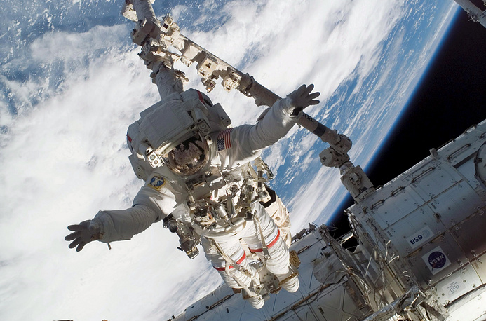 Over the next years the station continued to expand. Mobile Servicing System, or robotic system Canadarm2, was launched to the ISS in 2001. Photo: Astronaut Rick Linnehan, anchored to a Canadarm2 mobile foot restraint, as he participates in spacewalk, 2008