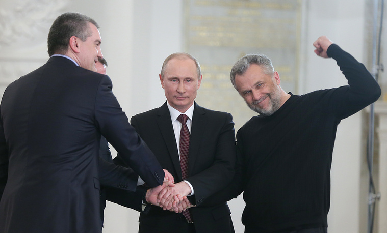 Crimea's Prime Minister Sergei Aksyonov, Russian President Vladimir Putin and Sevastopol Mayor Alexey Chaly shake hands after the signing of the agreement on the accession of the Republic of Crimea to the Russian Federation
