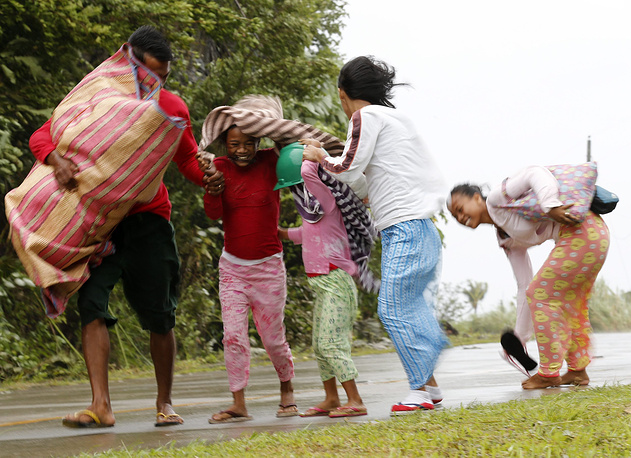 Tens of thousands of people fled their homes in the Philippines and thousands more were stranded after flights and sea travel were cancelled ahead of a powerful typhoon's expected landfall. Photo: Filipino residents evacuate to safer ground, Samar island, Philippines, 06 December 2014