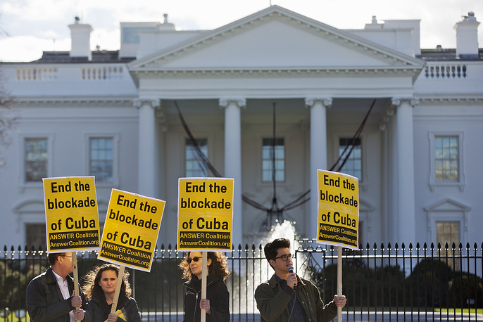 """Photo: People from the ANSWER Coalition (Act Now to Stop War and End Racism) hold signs urging the US to """"End the blockade of Cuba,"""" during a demonstration outside of the White House in Washington, December 17, 2014"""