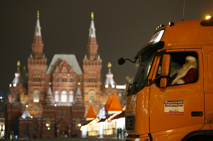 Photo: Father Frost (Russian Santa Clause) driving a timber truck with the main Russian New Year tree