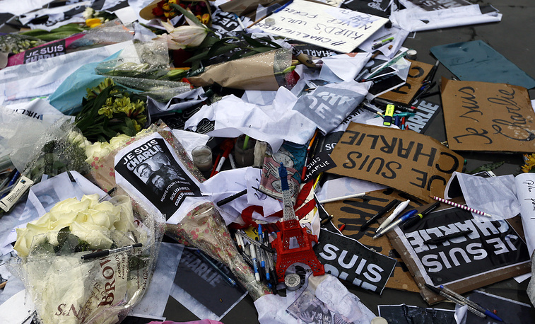 Flowers and pens and placards lie after being placed to show solidarity with those killed in an attack at the Paris offices of Charlie Hebdo, in Trafalgar Square, London
