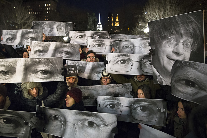 Mourners hold signs depicting victim's eyes during a rally in support of Charlie Hebdo at Union Square in New York, USA