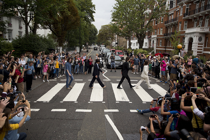 "The cast of the West End Beatles musical show ""Let it Be"" attempting to recreate the cover photograph of the Beatles album ""Abbey Road"" on the zebra crossing on Abbey Road in London"