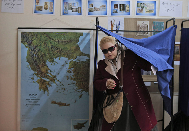 Photo: A woman at a polling station during early general elections in Greece