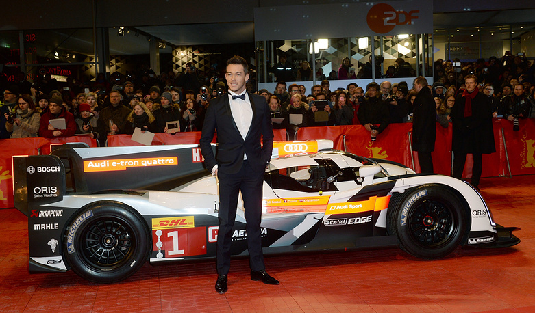 German race car driver Andre Lotterer in front of an Audi Le Mans race car during his arrival for the opening gala of the 65th Berlin Film Festival