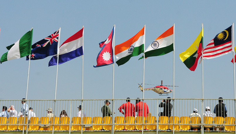 An Indian Air Forces' Hindustan Aeronautics Limited (HAL) helicopter of the Sarang team flying past national flags at the Yelahanka air base in Bangalore, India