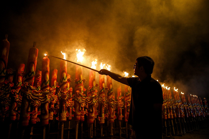 A man lighting a giant joss stick on the eve of the Chinese Lunar New Year celebrations at a temple in Kajang, outside Kuala Lumpur, Malaysia