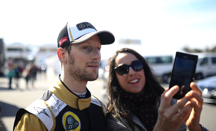 Romain Grosjean of France and Lotus in the paddock with a fan during the 2015 Formula One testing in Spain