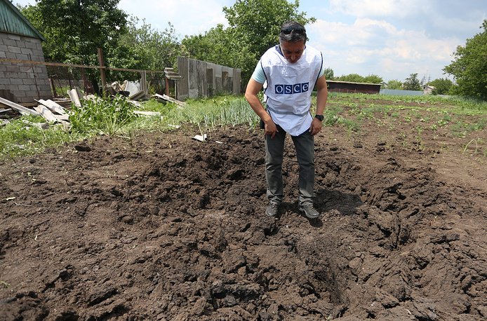 An OSCE observer standing at a site of a shell crater in the village of Telmanovo