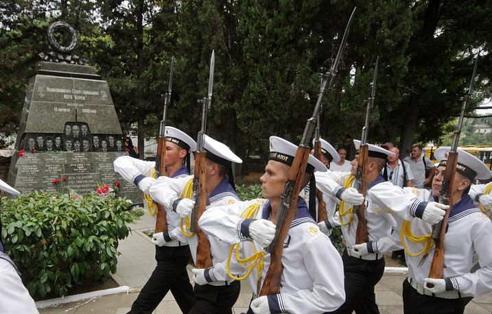 Russian navy officers participating in a commemorative event near a monument to crewmembers of the Kursk nuclear submarine