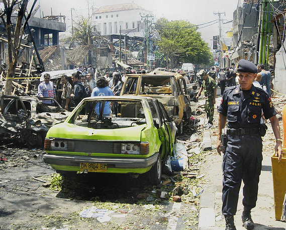 2002 Bali bombings. The attack killed 202 people in the tourist district of Kuta on the Indonesian island of Bali on 12 October 2002. Photo: Police officers near the ruins of a nightclub after a bomb blast destroyed it, Denpasar, Bali, Indonesia