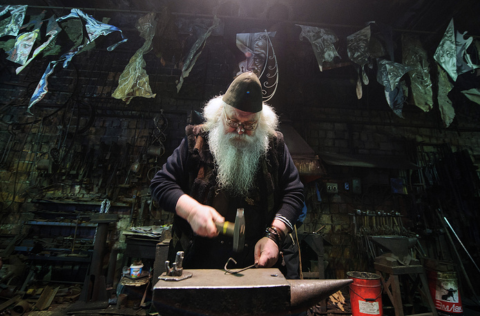 "Blacksmith Alexander Lysyakov minting a souvenir coin bearing an image of Russia's President Vladimir Putin and reading ""Everything will be alright"", at his workshop, February 20, 2015"