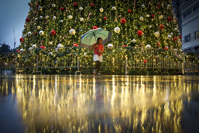 A girl walking in front of a Christmas tree at a mall in Kuala Lumpur, Malaysia