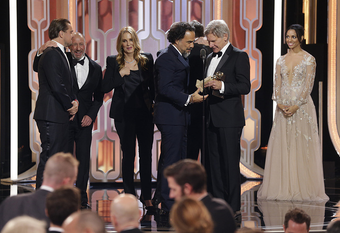 "Director Alejandro G. Inarritu accepting the award for best motion picture drama for ""The Revenant"", from presenter Harrison Ford"